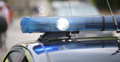 Spot light and blue flashing lights of the police car in the city Stock Photos