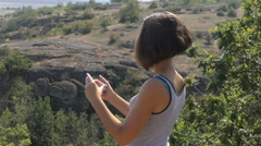Woman taking self portrait photo in canyon Stock Footage
