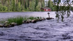 Wooden cross and stones in the middle of a Nordic river Stock Footage