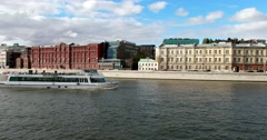 Pleasure boat sails along the Moscow river, the old houses on the shore Stock Footage