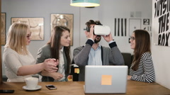 Handsome man tries app for VR helmet virtual reality glasses his friends and Stock Footage