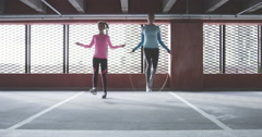 Two fit women skipping in rough urban enviroment Stock Footage