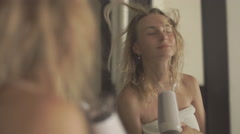 Woman drying her hair in bathroom in front of a mirror Stock Footage