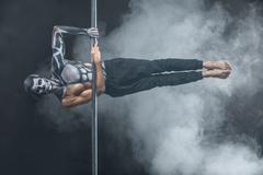 Male pole dancer posing in dark studio Stock Photos