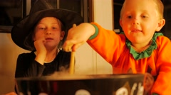 Witch and pumpkin making a magic potion in a pot. Stock Footage