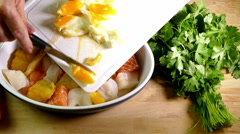 Pieces of boiled egg being added to fish pie mix in a bowl. Stock Footage