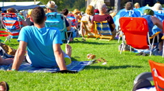 4K People Seated on Grass Lawn at Concert Music Festival, Live Community Crowd Stock Footage