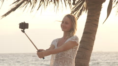 Funny girl standing in the sea and making the selfie photo on the phone using Stock Footage