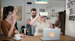 Blond girl tries app for VR helmet virtual reality glasses her friends and Stock Footage