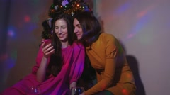 Female couple sitting near Christmas tree with glasses of wine watching videos Stock Footage