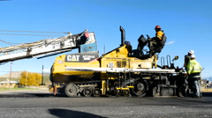 Asphalt paving machine road construction-workers shovel hot asphalt to low spots Stock Footage