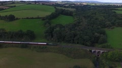 Long aerial shot following a steam train through the countryside. Stock Footage