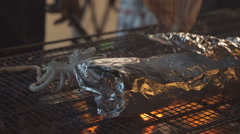 Video of flame grilled charcoal squid, night market street food Stock Footage