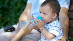 Child quenches thirst with water from a bottle Stock Footage