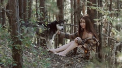 Attractive young woman sitting in the wild with beautiful dog Stock Footage