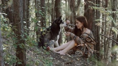 Attractive fair-skinned young woman sitting and playing with her husky dog Stock Footage