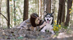 Portrait of eye-catching girl lying in the forest with her dog Stock Footage