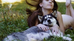 Enigmatic young woman lying with her dog on meadow gazes intently at something Stock Footage