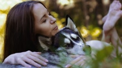Attractive fair-skinned girl lying with closed eyes and hugging the husky dog Stock Footage