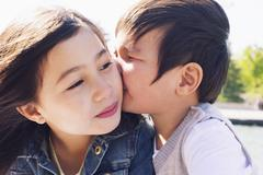 Little boy kissing his sister's cheek Stock Photos