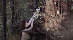 Young woman in wild clothes holding the wolf-looking dog on its paw Stock Footage