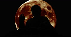 Silhouettes of the Budda with giant moon Stock Footage