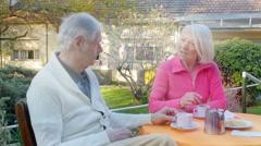 Elder couple having breakfast on a beautiful garden. Age, medicine, support, Stock Footage