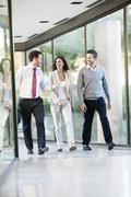Businessman engaged in walk and talk with associates Stock Photos