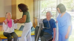 Elder woman and man at the gym. Exercising with weights and cyclette, helped by Stock Footage