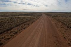Dirt road through arid landscape Stock Photos