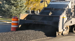 Hot asphalt augered into conveyor to paving machine road constructio Stock Footage