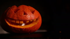 Man starts fire in Halloween Jack-o'-lantern .Horror smile lights in the dark Stock Footage