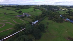 Aerial shot following a steam train in the countryside. Stock Footage