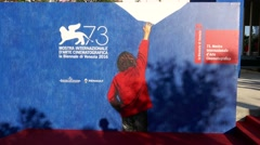 People walking in front of the poster of 73th Venice international film festival Stock Footage