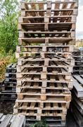 Wooden pallets / wooden pallet overlap in warehouse / Stock Photos