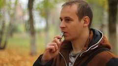 Man smoking electronic sigarette outdoor Stock Footage