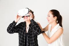 Young female friends playing with virtual reality simulator Kuvituskuvat