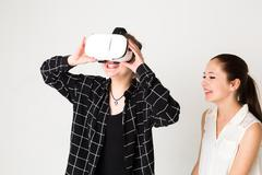 Two cute amused teenage girls testing virtual reality camera system Kuvituskuvat
