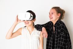 Amused teenage girls testing virtual reality camera system Kuvituskuvat
