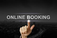 Business hand pushing online booking button on black blurred background Stock Photos