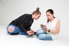 Two teenage girls sitting on the floor assembling a little metal model Stock Photos