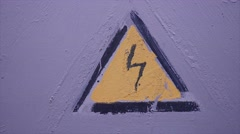 Sign of the lightning current triangle gently on a gray wall Stock Footage