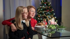 Little girl sitting on granny's lap on Christmas Stock Footage