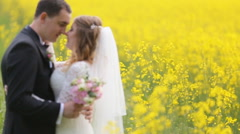 Husband and wife in wedding dress and suit smiling and standing among yellow Stock Footage
