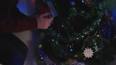 Young man sneaking up to Christmas tree and placing a gift Stock Footage