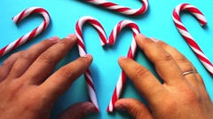 Heart of striped candy canes made by hand on a blue surface Stock Footage