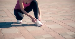 Young woman tying running shoes lace before jogging 4k video. Female fitness Stock Footage