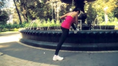 Woman stretching leg muscle park fountain slow motion HD video. Fitness exercise Stock Footage