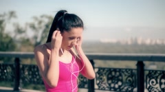 Runner woman putting headphones in ear HD video. Female turn music start running Stock Footage