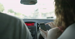 4K Couple in car driving through the city, using smartphone as navigation device Stock Footage